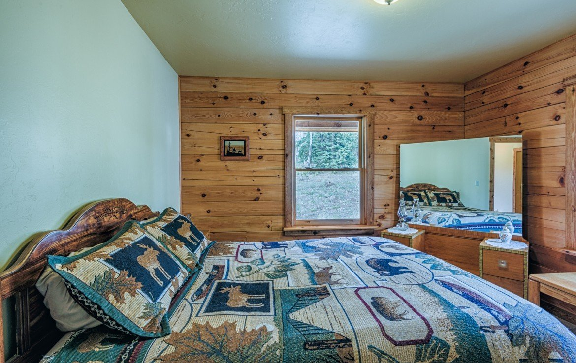 Bedroom with Wood Paneling - 58002 Elk Dr Montrose, CO 81403 - Atha Team Realty