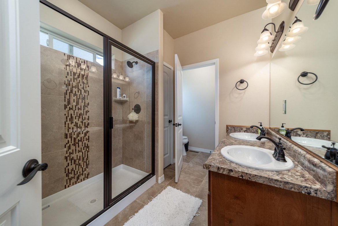 Primary Bathroom with Tiled Shower - 597 Cobble Dr Montrose, CO - Atha Team MLS Colorado